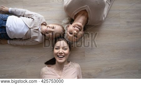Happy Family Grandmother Mother And Preteen Girl Lying On Floor