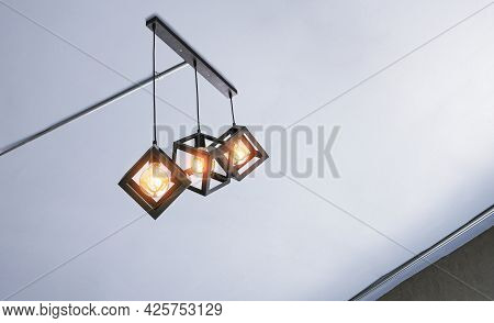 Low Angle View Of Illuminated Modern Three Metal Cage Hanging Lamps With Electrical Conduit Pipes On