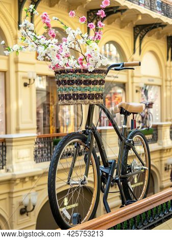 Close-up Of A Bicycle With A Basket Of Flowers In A Shopping Center . A Beautiful Decorative Element