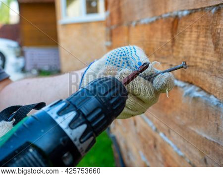 A Beginner Tries To Use An Electric Screwdriver To Screw A Nail Into The Wall. Errors In The Use Of