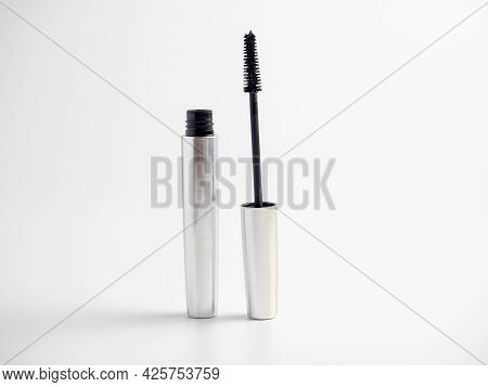 Mascara In A Silver Tube Stands On A White Background. Brush For Applying Mascara. Cosmetology, Self