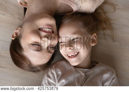 Happy Mother And Preteen Daughter Lying On Warm Floor Smiling