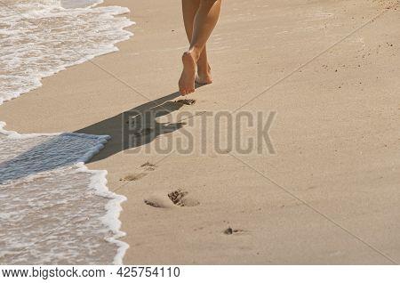 A Woman Walking Barefoot On Long Beach In Batu Ferringhi Penang Malaysia.