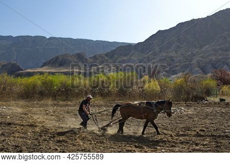 Hebda. Russia. North-eastern Caucasus. April 08, 2021. A Young Peasant Plows The Land With An Iron P