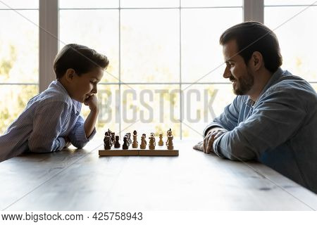 Focused Thoughtful Clever Son And Dad Playing Chess