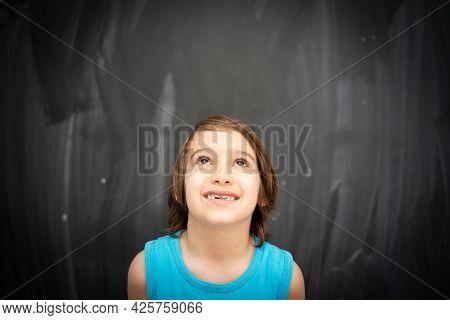 Little Cute Boy In Front Of Classroom Chalkboard