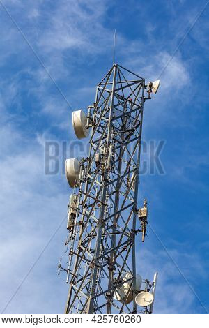 Cellular Antenna On A Background Of Blue Sky In Sunny Weather. Comunication.