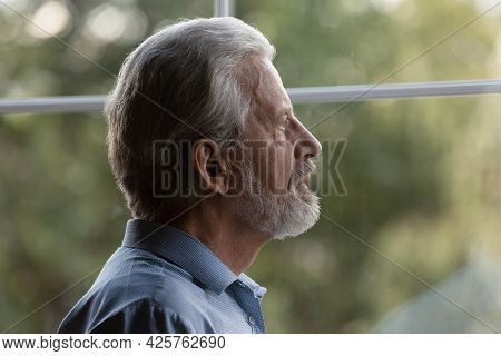 Sad Senior 70s Man Lost In Thoughts Looking Out Window