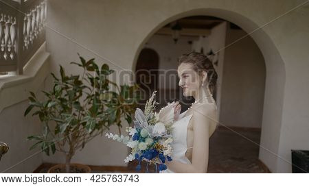 Beautiful Bride With Bouquet Poses On Background At Home. Action. Young Bride In Elegant Dress Smile