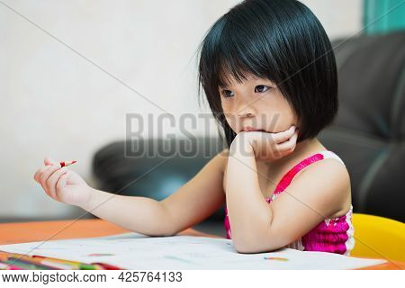 Asian Kindergarten Girl Is Studying At Home In Boredom. Because Studying All Day Long, It's Too Hard