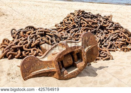 Rusty Anchor Chain With Ship Anchor Of An Old Ship On The Sand Beach