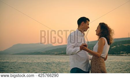 Man And Woman Holding Hands And Looking To Each Other. Couple At Romantic Date During Sunset. Hetero