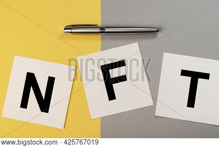 Nft Acronym On Paper Notes On Yellow And Gray Background.