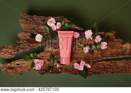 Pink Tube Of Cosmetic Cream On Wood Background With Pink Flowers Roses. Stylish Look Of The Product,
