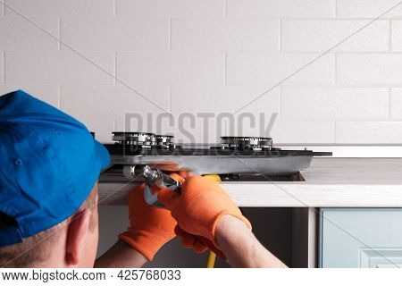 Serviceman Connects  Gas Hose To  Hob, Hands With An Adjustable Wrench Close-up