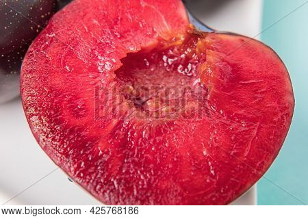 On A White Saucer Is A Large Plum, Cut In Half, And Next To It Is A Whole Plum.