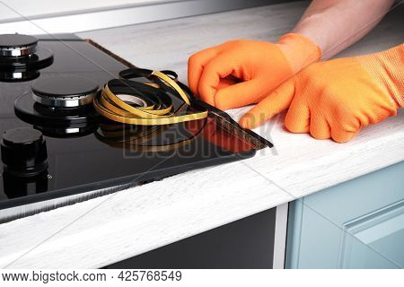 Serviceman Sticks The Seal On The Kitchen Countertop Before Installing The Gas Hob