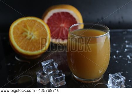 The Juice Of Orange Abicos Yellow In The Glass Next To Lie Half Of Orange And Grapefruit Ice On A Bl