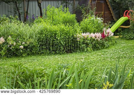 A Beautiful View Of A Lush Green Garden Landscape With A Blend Of Planter And Green Lawn Areas In Sp