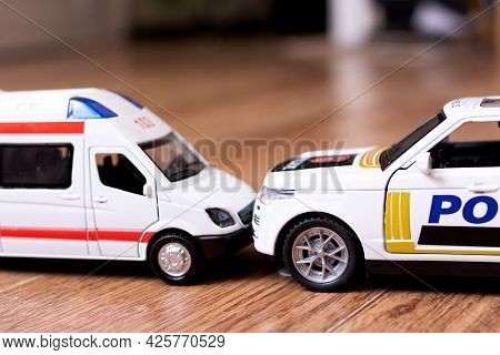 Collision Of Toy Ambulance Cars And Police On Wooden Floor Closeup