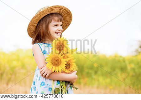 Outdoor Portrait Of Adorable Little Girl In Straw Hat And Blue Dress Is Walking In A Field Of Sunflo