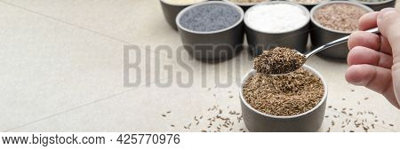 Caraway Seeds. Spoon With Caraway Seeds In Hand Against A Background Of Various Seeds In Black Conta