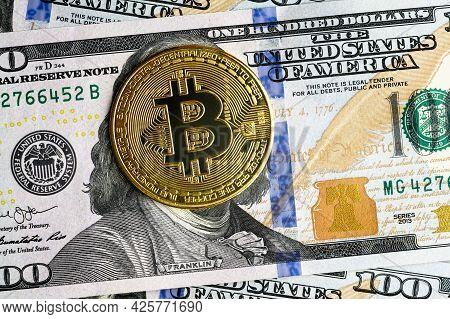 Bitcoin Vs Us Dollar, Gold Bit Coins On 100 Dollar Bill. Digital Crypto Currency Bitcoin Hides Frank