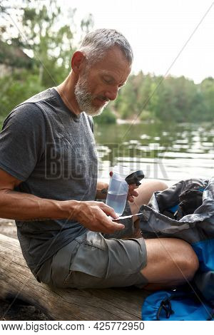 Middle Aged Caucasian Man Distillating Water For Drinking Using Pills While Sitting On Log Near Lake