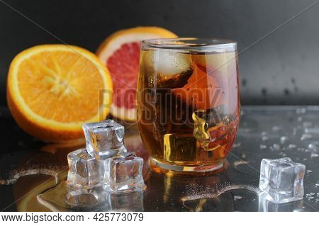 Apple Citrus Dark Juice In A Glass Next To Lies Citrus Orange Grapefruit Ice On A Black Background.