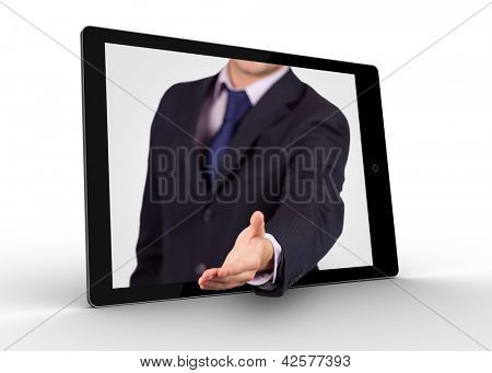 Businessman reaching out from digital tablet for handshake on white background