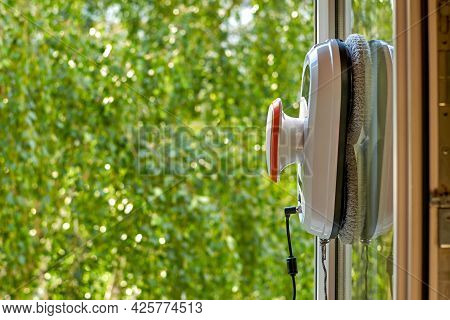 A Robot Window Cleaner. Robot Vacuum Cleaner Cleans A Dirty Window. Smart Robots For Cleaning Window