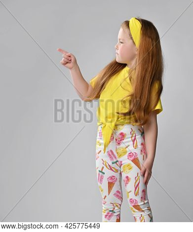 Cute Serious Little Red-haired Girl Child Wearing Summer Fashion Outfit Pointing Finger Aside At Cor