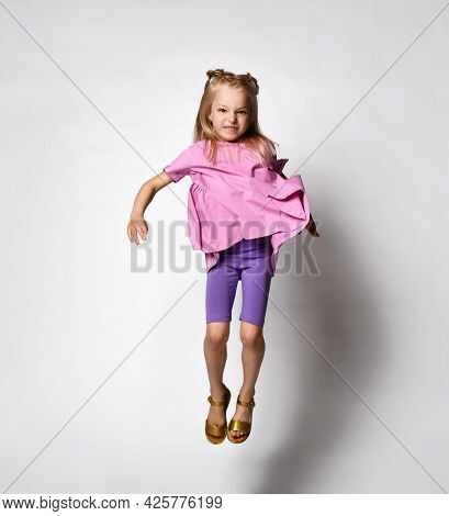 Happy Little Girl In Bright Purple And Pink Summer Clothes Is Jumping For Joy On A White Background.