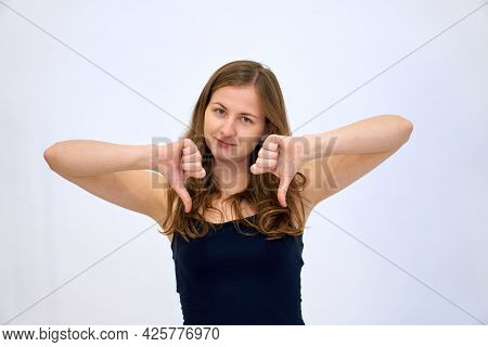 No Thumbs Down. The Woman Denies And Refuses. Beautiful Caucasian Woman Stands On A White Background