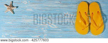 Yellow Rubber Beach Flip Flops On A Blue Wooden Background