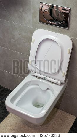 Wall-mounted White Toilet With Built-in Flush System. Modern Toilet.