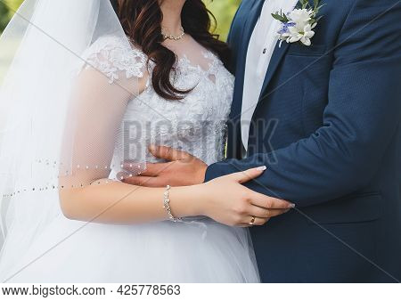 The Hands Of The Bride And Groom Hug Each Other. Tenderness And Hugs Of A Man And A Woman At A Weddi