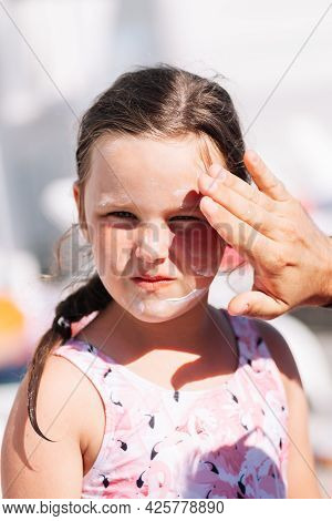 The Fathers Hand Applies Sunscreen From Burns And Ultraviolet Light On The Daughters Face On A Hot S
