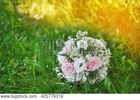 Wedding Bouquet Of Bride Of Light Flowers Roses Lies On The Grass In The Outdoor Park.