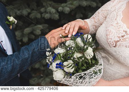 The Bride And Groom Put Their Hands On The Wedding Bouquet Of Flowers Of White Roses, Close-up Of Te