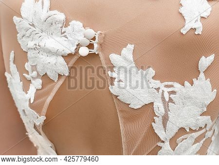 Applique From Behind On The Back Of The Bride's Wedding White Pattern Dress, Close-up.
