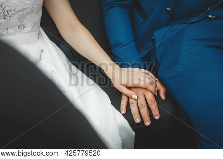 The Hand Of The Bride In A White Dress Is Put Or Holds The Groom's Hand.