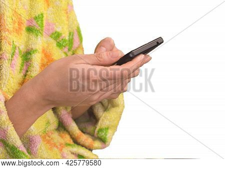A Girl In A Robe Holds A Smartphone And Spends Time In A Mobile Phone On A White Background, Isolate