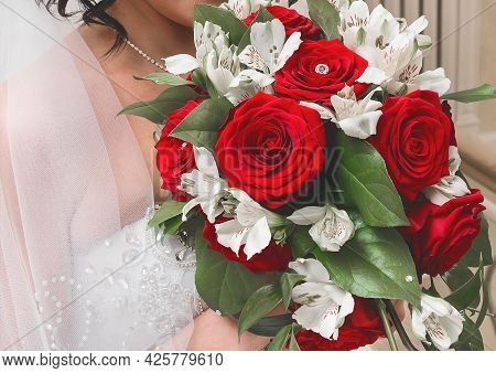 Bride In A White Wedding Dress With A Veil Holds A Bouquet Of Beautiful Flowers Of White And Red Ros