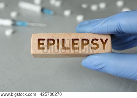 Doctor Holding Wooden Block With Word Epilepsy At Grey Table, Closeup