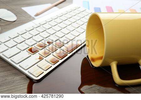 Cup Of Coffee Spilled Over Computer Keyboard On Wooden Office Desk, Closeup