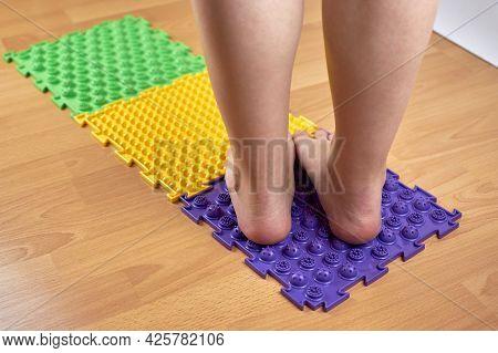 Orthopedic Massage Mat. Women's Feet Standing On An Orthopedic Mat. Prevention Of Flat Feet.
