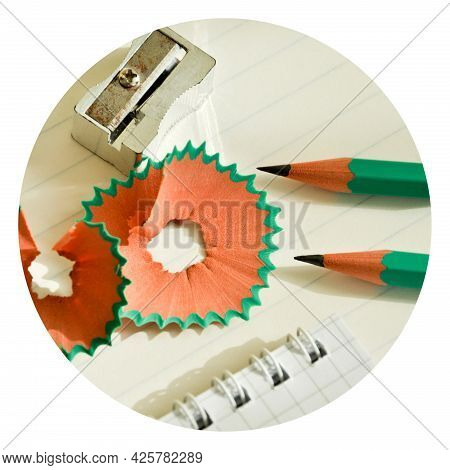 Green Wooden Pencils And Notepad Opened With Pencil Sharpener On White Lined Paper