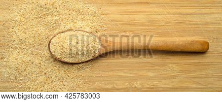 Fresh And Tasty Bread Crumbs Galeta Flour In Wooden Spoon On Brown Bamboo Cutting Board
