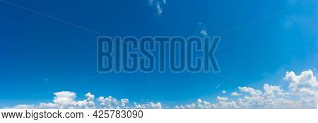 Blue Sky Panorama With White Clouds With Copy Space. A Wide Shot Of Clear Skies With Summer Fluffy C
